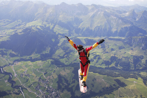 High angle view of skydiver surfing on sky board over mountains - CUF07520