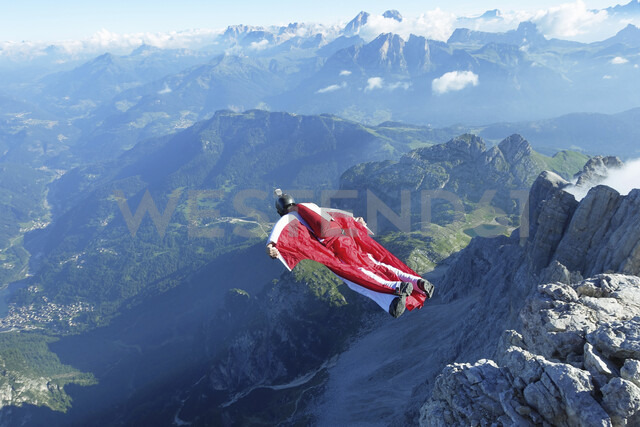 Male wingsuit BASE jumper taking off from cliff edge - CUF07523 - Oliver Furrer/Westend61