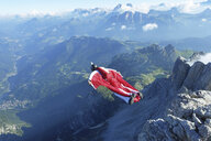Male wingsuit BASE jumper taking off from cliff edge - CUF07523
