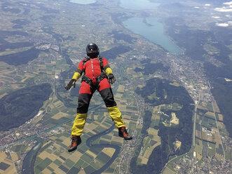 Female skydiver free falling on back above landscape - CUF07526