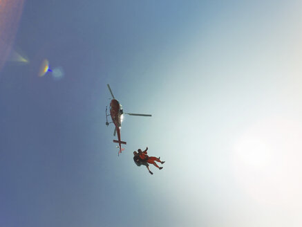 Low angle view of tandem skydiving jump from a helicopter  against sunlit blue sky - CUF07529
