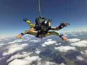Portrait of tandem skydivers free falling above clouds and landscape - CUF07532
