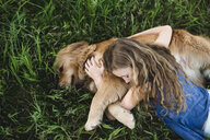 Overhead view of girl lying on grass hugging golden retriever dog - CUF07669