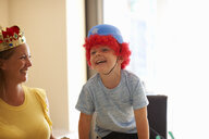Mother and son playing dress up, wearing funny hats, laughing - CUF07672