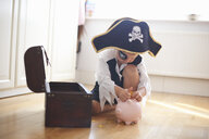 Young boy dressed as pirate, putting money into piggy bank - CUF07675