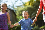 Siblings holding hands running in garden - CUF07681