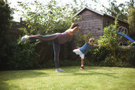 Mother and son exercising in garden, standing in yoga position - CUF07696