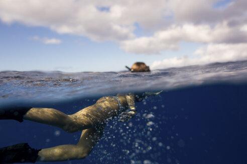 Woman wearing flippers swimming underwater, Oahu, Hawaii, USA - ISF01460