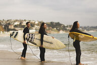 Three friends standing in sea, holding surfboards, preparing to surf - ISF01508
