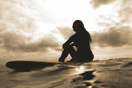 Young woman in sea, sitting on surfboard - ISF01511