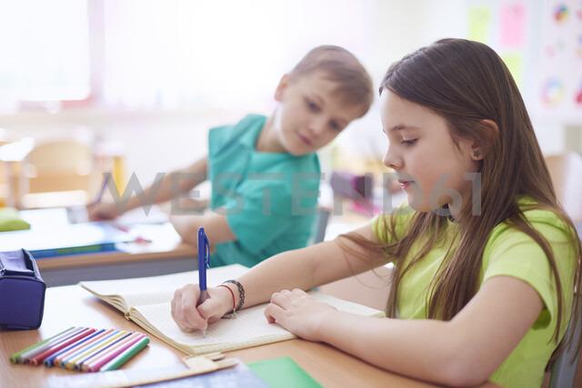 Schoolboy looking at schoolgirl writing in exercise book in class - ABIF00366