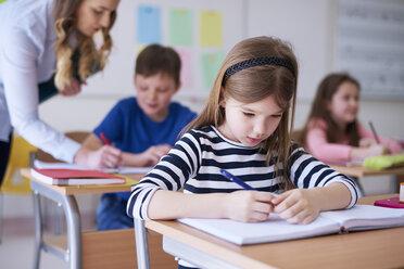 Schoolgirl writing in exercise book in class - ABIF00372