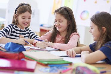 Happy schoolgirls working together in class - ABIF00381