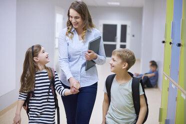 Smiling pupils and teacher walking hand in hand on corridor in school - ABIF00384