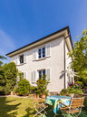 Germany, Stuttgart, one-family house, garden table with lawn chairs - WDF04659
