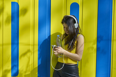 Young woman listening music with headphones and water bottle text messaging - BEF00066
