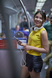 Portrait of smiling young woman with cell phone and headphones in underground train - BEF00069