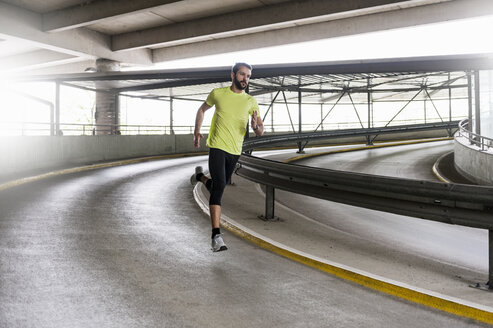 Man running in parking garage in a curve - DIGF04264