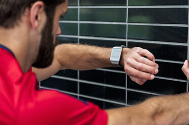 Man having a break from running checking the time on a smartwatch - DIGF04270