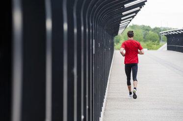 Rear view of man running on a bridge - DIGF04273