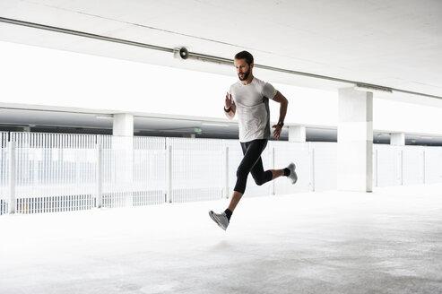 Man running in parking garage - DIGF04291