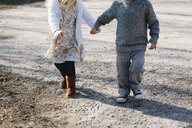 Siblings holding hands walking on gravel road - ISF01560