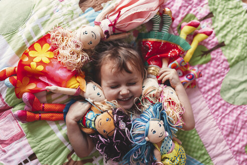Girl lying on bed surrounded by rag dolls - ISF01569