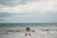 Girl praying on beach, Cancun, Mexico - ISF01623