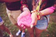 Pink chalk cupped in young woman's hands at festival - ISF01650
