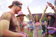 Young adult friends dancing covered in coloured chalk powder at festival - ISF01656