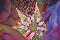 Overhead view of young adults in circle covered in coloured chalk powder at festival - ISF01659