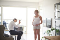Man taking smartphone photograph of pregnant girlfriend in living room - CUF07798