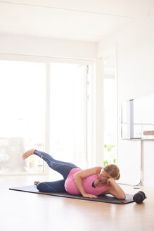 Pregnant young woman exercising on yoga mat in living room - CUF07810