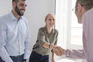 Businesswoman and man shaking hands at boardroom table - CUF07819