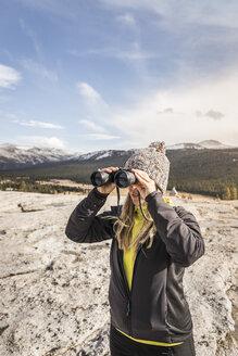 Woman looking through binoculars, Yosemite National Park, California, USA - CUF07870