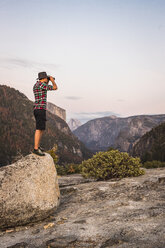Man standing on boulder looking through binoculars, Yosemite National Park, California, USA - CUF07873