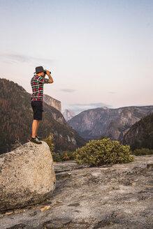 Man standing on boulder looking through binoculars, Yosemite National Park, California, USA - CUF07873