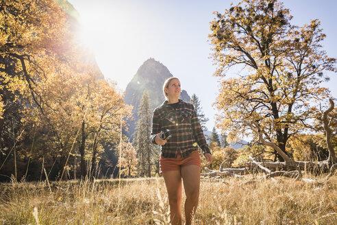Woman with camera in autumn landscape, Yosemite National Park, California, USA - CUF07876