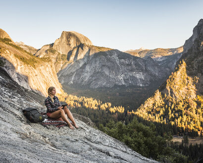 Woman on rock looking out at valley forest, Yosemite National Park, California, USA - CUF07879