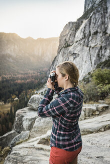 Woman photographing landscape from rock formation, Yosemite National Park, California, USA - CUF07882