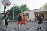 Friends on basketball court playing basketball game - CUF07975