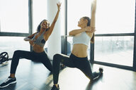 Two young women exercising in gym, doing lunges - ISF01730