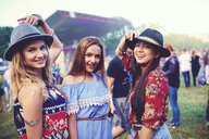 Portrait of three young female friends in trilbies at festival - ISF01763