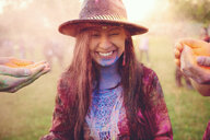 Hands covering young boho woman with coloured chalk powder at festival - ISF01778