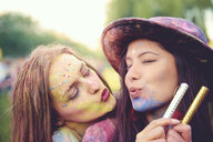 Portrait of two young women covered in coloured chalk powder puckering lips at festival - ISF01784