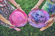 Waist down view of two young women holding felt hats covered in coloured chalk at festival - ISF01787