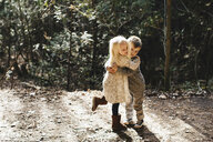 Siblings hugging and playing on gravel road - ISF01811