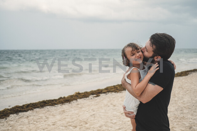 Father kissing daughter on beach, Cancun, Mexico - ISF01916 - Kymberlie Dozois Photography/Westend61