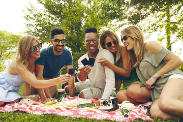 Five adult friends looking at film from instant camera at picnic in park - ISF01952