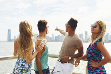 Four adult friends pointing at skyline from waterfront, New York, USA - ISF01964